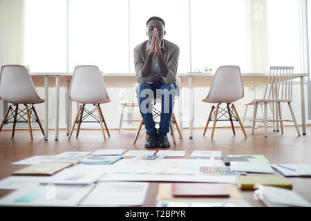 Full length portrait of contemporary African businessman planning creative project in office with papers laying on floor, copy space - Stock Photo