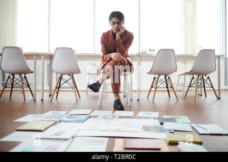 Full length portrait of contemporary Middle-Eastern businessman planning creative project in office with papers laying on floor, copy space - Stock Photo