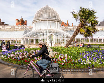Belfast, Northern Ireland, UK - March, 23 2019: Botanic Gardens on a Spring day. A woman cycles past the Palm House - Stock Photo