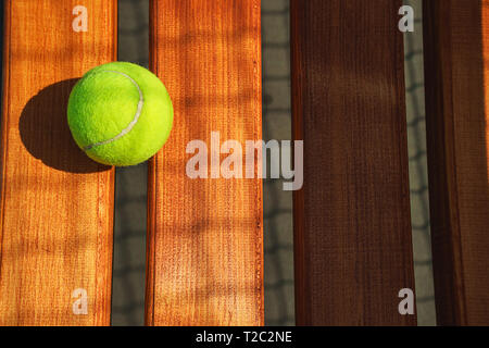 Tennis ball on the bench on court. Concept of sport, healthy lifestyle. - Stock Photo