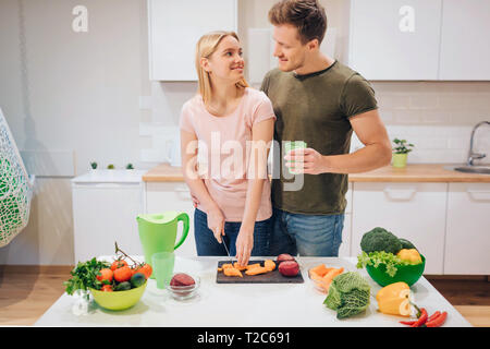 Vegan loving family cooking raw vegetables in the kitchen. Young woman cutting vegetable while her husband drinks detox tea in morning. Diet detox - Stock Photo
