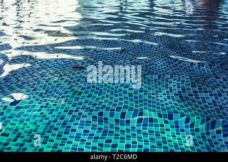 A close up of a clean swimming pool water at the light-blue tiled floor background. One swimming pool drain under rippling indoor pool water. A shallo - Stock Photo