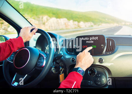 male hands with smart watch on switching on auto pilot mode on car display on highway - Stock Photo