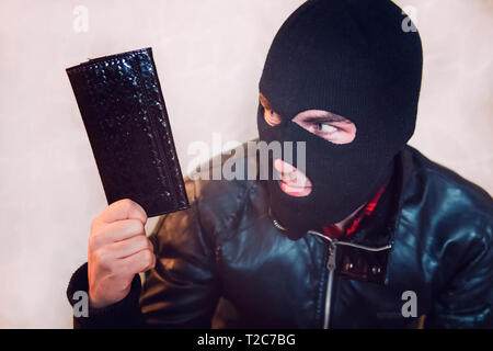 Young ill-intended man wearing black mask holds the black leather women purse and looks to his loot. Robber has stolen the wallet. Half shot of a thie - Stock Photo