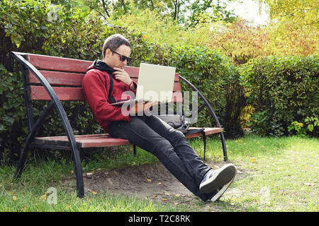 Young stylish male student texting message on laptop in park on autumn. The guy works at a laptop in the open air. Remote work. Thoughtful young man l - Stock Photo