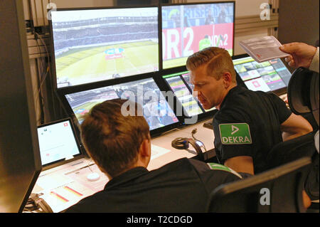 31 March 2019, North Rhine-Westphalia, Köln: Football Bundesliga - video evidence, visit to the Video Assist Center during live football Bundesliga coverage. Video assistants Mark Borsch (l) and Tobias Welz (r) sit in their seats. Photo: Henning Kaiser/dpa - Stock Photo