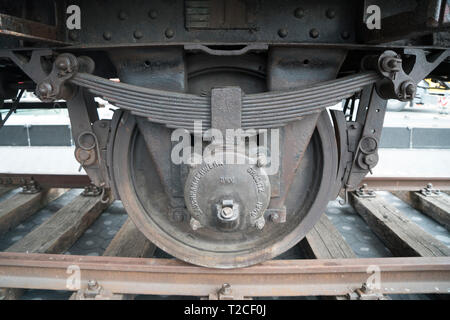 """New York, USA. 31st Mar, 2019. New York, NY.  The wheel of a German National Railroad freight car that was installed on the plaza in front of the Museum of Jewish Heritage in Battery Park City, Manhattan, New York on the morning of March 31 as part of the museum's upcoming exhibition, """"Auschwitz. Not long ago. Not far away."""" This freight car, which would have been packed with 80 to 100 people, was one of many that the Nazis employed to transport people — most of them, Jews — to Auschwitz to be killed. Credit: Terese Loeb Kreuzer/Alamy Live News - Stock Photo"""