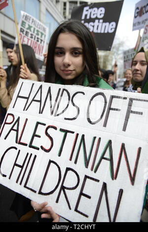 London, Greater London, UK. 30th Mar, 2019. A protester is seen holding a placard that says Hands off Palestinian children during the Exist, Resist, Return Rally for Palestine in London.People gather outside the Israeli embassy in London to demonstrate against the Israeli government, and to demand respect for Palestinians' fundamental rights to exist, resist and return. Palestinians are calling for global protests to support their right to come back to their villages. Rally was organized by Palestine Solidarity Campaign, Stop the War Coalition, Palestinian Forum in Britain, Fr - Stock Photo