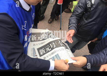 People try to receive a copy of extra edition of a newspaper reporting the name of the new Imperial era, 'Reiwa,' in Tokyo, Japan on April 1, 2019. The Japanese government officially announced the country's next era will be known as the 'Reiwa' era on Monday, a month before Crown Prince Naruhito ascends the throne following Emperor Akihito's abdication. Credit: AFLO/Alamy Live News - Stock Photo