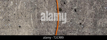 gray rough concrete surface wall and orange colored electrical cable. Web banner for design. - Stock Photo