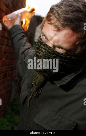 Masked man brandishing a petrol bomb - Stock Photo