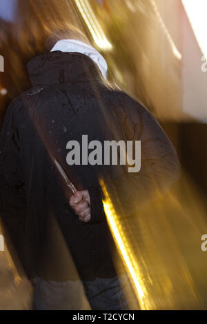 Knife crime. Hooded man brandishing a butterfly knife - Stock Photo