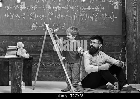 Smiling teacher with long beard in glasses sitting on the floor while kid is having fun. Little schoolboy wiping chalkboard. - Stock Photo
