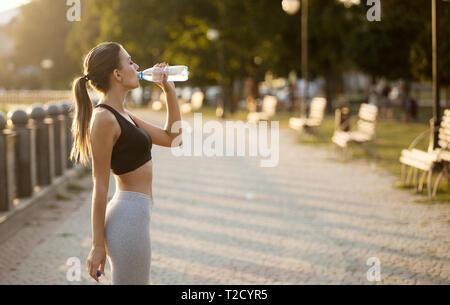 Sportswoman making break in jogging, drinking water on quay in park, copy space - Stock Photo