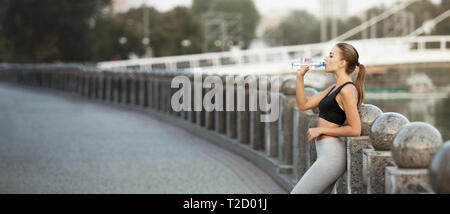 Workout break. Sporty millennial woman drinking water after run practice on bridge, panorama with copy space - Stock Photo