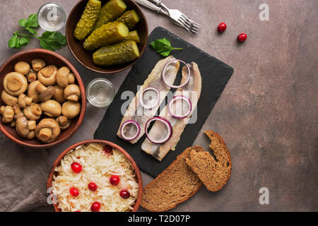 Traditional Russian snacks and vodka, sauerkraut with cranberries, herring, pickled cucumbers, pickled mushrooms and rye bread on a brown background.  - Stock Photo