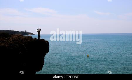 Man on the edge of the cliff, Tarragona, Spain. - Stock Photo