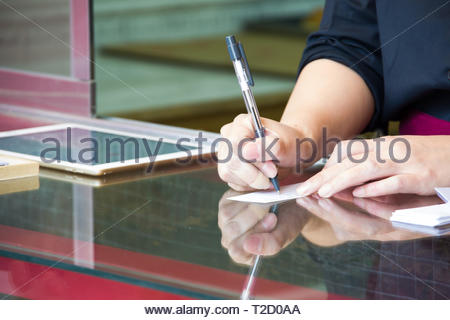 Woman writing with a pen on a piece of paper on a shop window in japan. - Stock Photo