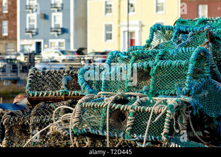 Crab pots or creels stacked on the quayside of Arbroath harbour with The Shore in the background, Angus, Scotland. - Stock Photo