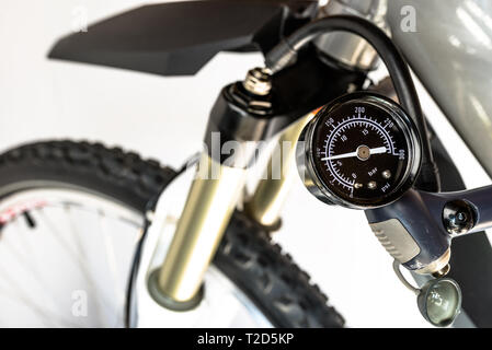 Pumping of the front, bicycle oil-air shock absorber using a specialized hand pump, visible pressure indicator in units of bar / psi. - Stock Photo