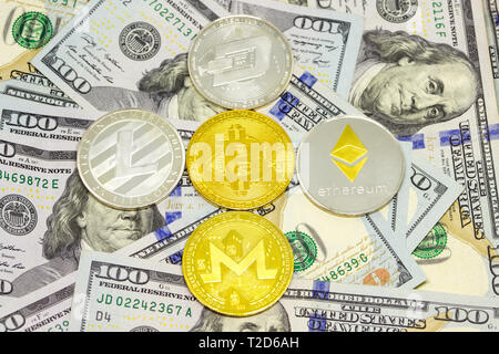 Cryptocurrency coins displayed with bitcoin in the middle on a heap of one hundred dollar bills. - Stock Photo