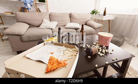 After party interior chaos. Beer bottles, popcorn and pizza on table in room - Stock Photo