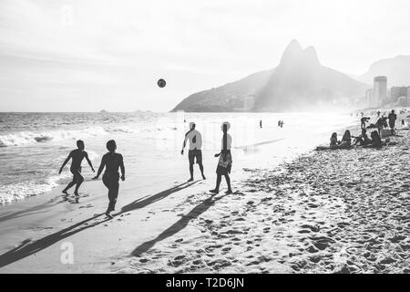 RIO DE JANEIRO, BRAZIL - FEBRUARY 24, 2015: A group of Brazilians playing on the shore of Ipanema Beach - Stock Photo