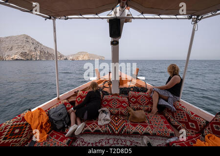 Cruise tour aboard a traditionally decorated arabian Dhow wooden boat along the rocky mountains of the Musandam peninsula in the Oman Fjords - Stock Photo