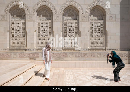 Tourist posing for photos at the Sultan Qaboos Grand Mosque, Muscat, Oman - Stock Photo