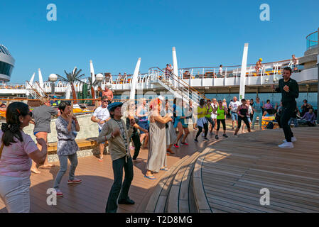 Passengers dancing on the deck of a cruise ship following the lead of a staff entertainer on stage during a dance class - Stock Photo