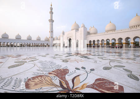 Sheikh Zayed Grand Mosque inner courtyard with ornate flower themed floor mosaics, Abu Dhabi, United Arab Emirates - Stock Photo