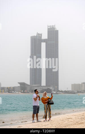 Young muslim woman wearing a hijab taking a selfie with a man at a beach in Abu Dhabi, United Arab Emirates - Stock Photo