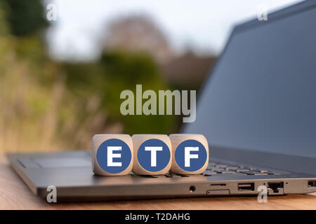 Cubes placed on a Notebook with the letters 'ETF' which stands for 'Exchange traded funds'. - Stock Photo