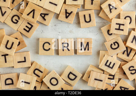 Top down view, pile of square wooden blocks with letters CRM stands for Customer Relationship Management on white board - Stock Photo