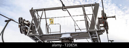 Steel ropes over wheels in mechanism on top of ski chairlift support column, number 6 on yellow plate, bright sky background, wide banner. - Stock Photo