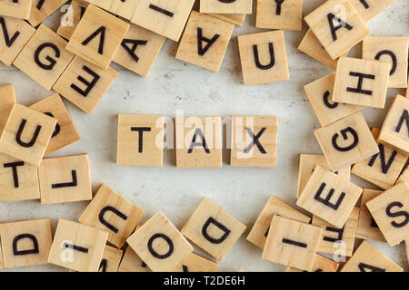 Top down view, pile of square wooden blocks with word TAX on white board - Stock Photo