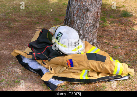 Fireman's heavy jacket and chief's white helmet of the Tucson Fire Dept laying in the shade under a tree away from the Arizona heat - Stock Photo