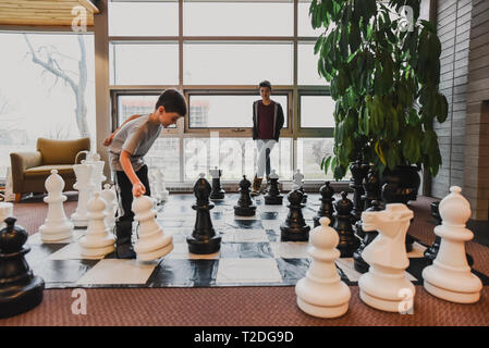 Two young boys playing game of chess with giant pieces in bright space - Stock Photo