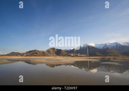 The Garfield Smelter Stack at Rio Tinto Kennecott smelter reflects in a tide pool on the beach on the southern shore of The Great Salt Lake, Utah, USA - Stock Photo