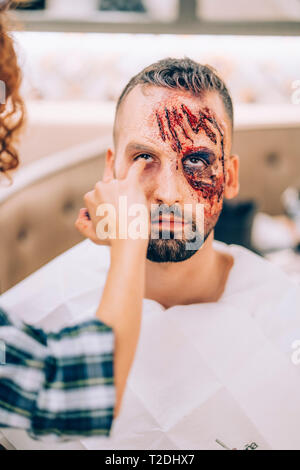 Man with makeup on his face with wounds and blood. - Stock Photo