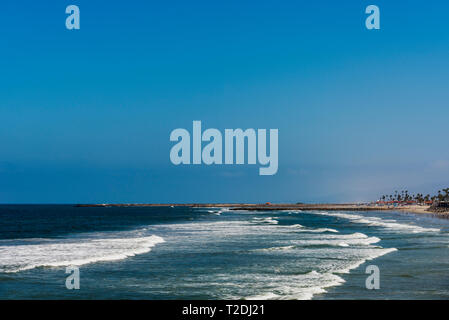Blue ocean with white waves breaking onto shoreline under bright blue sky. Sandy beach and trees. - Stock Photo