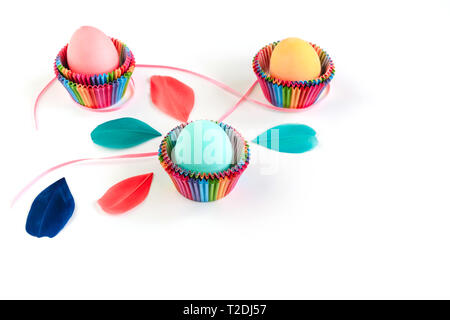 Bright creative Easter decoration of colorful eggs in raibow colored paper forms for cupcakes on white background decorated with feathers. Copy space. - Stock Photo