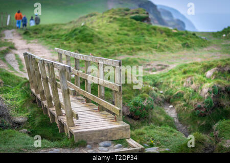 Walkers use a small wooden bridge to cross over uneven terrain on the popular South West Coast Path near Abbotsham in North Devon. - Stock Photo