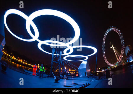 The Olympic Rings illuminate workers moving the, 'Rings on the River' exhibit, from Greenwich to the South Bank, during the London Olympic Games 2012. - Stock Photo