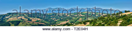 A beautiful panoramic view with blue skies over the hills of Le Marche, Italy, with Monti Sibilini in the background - Stock Photo