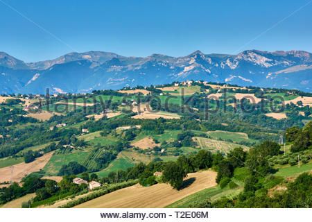A beautiful view with blue skies over the hills of Le Marche, Italy, with Monti Sibilini in the background - Stock Photo