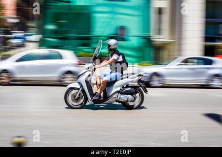 Messina, Sicily, Italy. A man on a scooter (with motion blur) on the street of Messina - Stock Photo