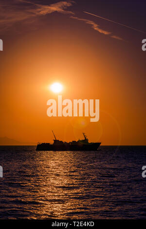 Large ferry boat at sunset on the Aegean Sea leaving Samothrace Island in Greece at sunset with lens flare in the shot - Stock Photo
