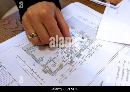Architect, engineer discussing blueprint of a house with its clients in the office - Stock Photo