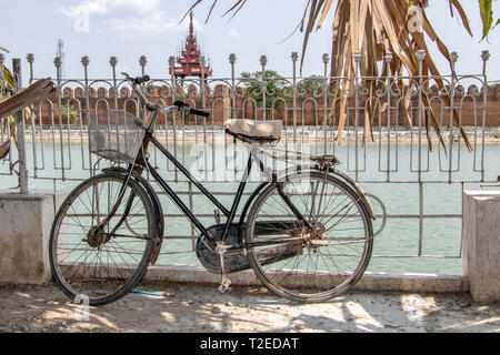 An old bicycle is lean on a railing over a water moat before the Royal Palace in Mandalay, Myanmar. - Stock Photo
